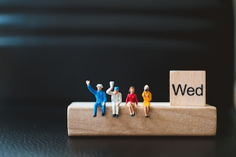 Miniature people, man and woman sitting with wednesday wooden block using as business concept