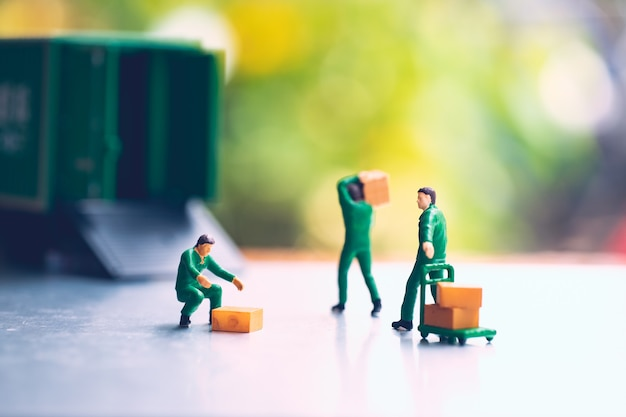 Miniature people, man carrying box using for logistic and business concept