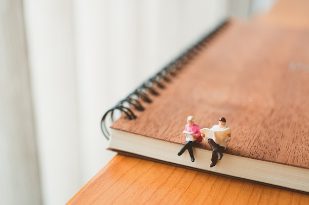 Miniature people, man and woman sitting on book using as education concept