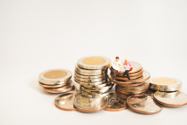 Miniature people man and woman sitting on stack coins using as business and finance concep