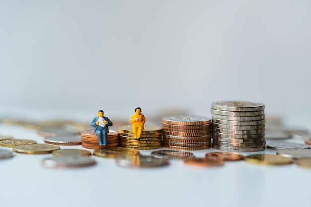 Miniature people, man and woman sitting on stack coins using as business and financial concept