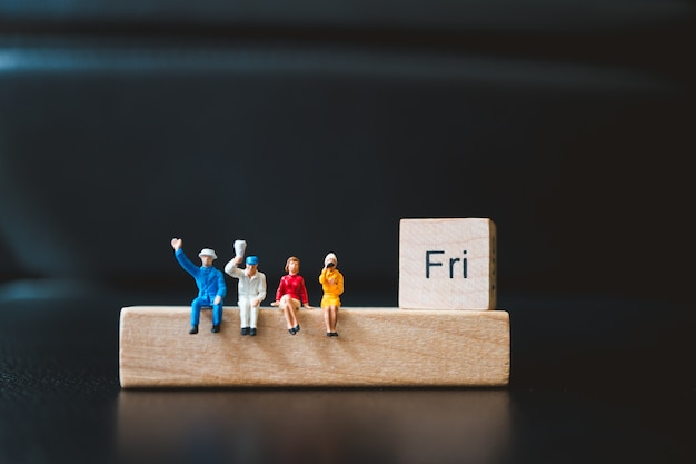 Miniature people, man and woman sitting with friday wooden block using as business concept