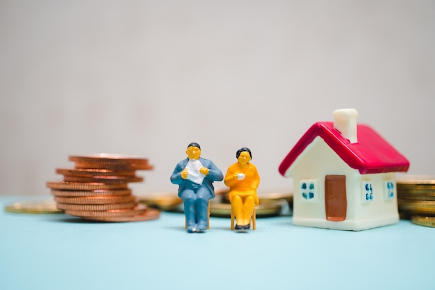 Miniature people, man and woman sitting with stack coins and mini house