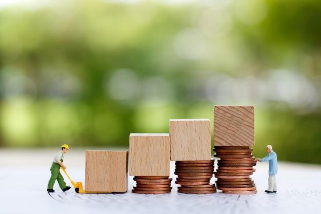 미니어처 사람들이 동전 스택에 나무 블록을 이동합니다.