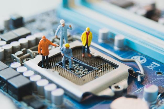 Miniature people network engineers at mainborad computer
