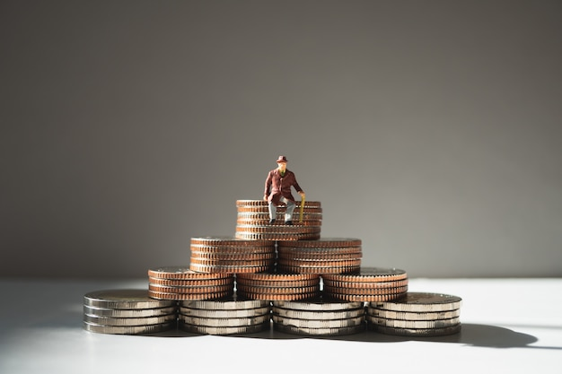 Miniature people, old man sitting on stack coins using as job retirement and insurance con