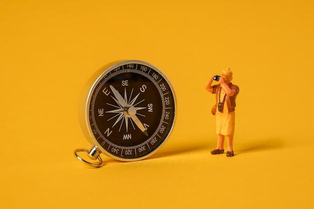 黄色の背景にミニチュアの人々は、コンパス旅行の概念の近くに立っている観光客