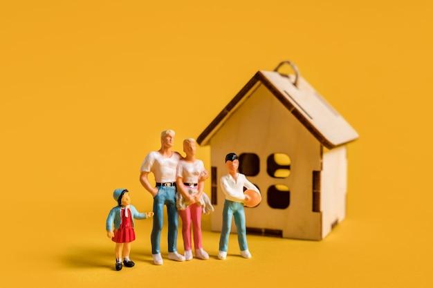Миниатюрные люди на желтом фоне молодая семья и недвижимость