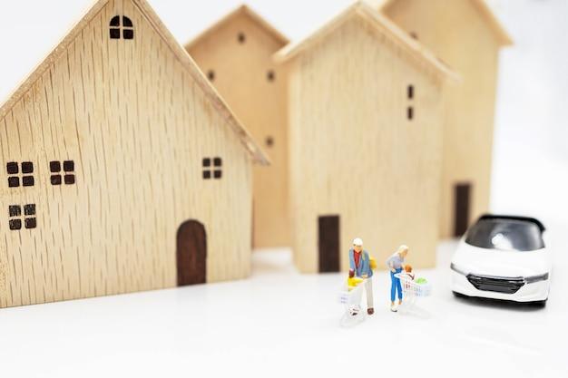 Миниатюрные люди: родители и дети с тележкой для покупок, стоящей на стопке монет с домом и автомобилем. понятие покупки жилья и транспортных средств.