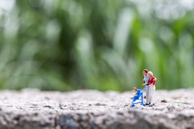 Miniature people:  parents with children walking outdoor