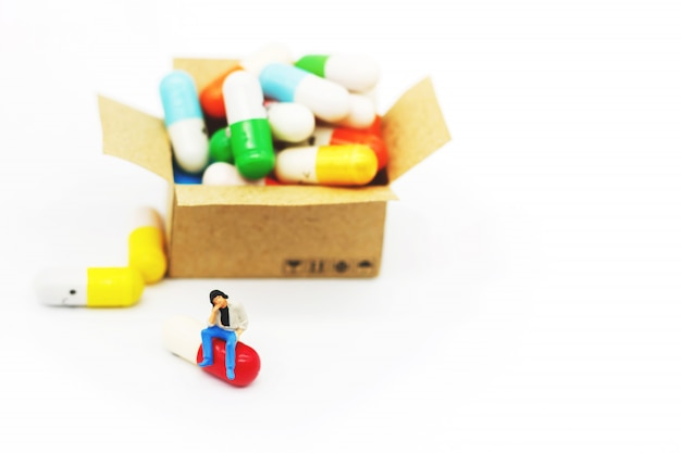 Miniature people: patients sitting on drugs. health care and business concept.