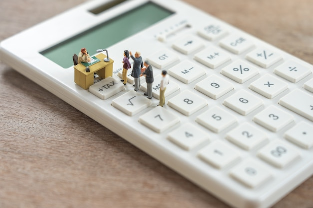 Miniature people pay queue annual income tax for the year on calculator.