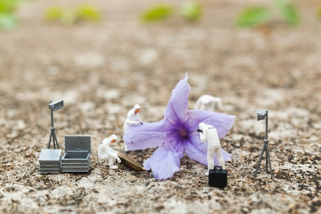 Miniature people: police and detective finding proof from flower in crime scene