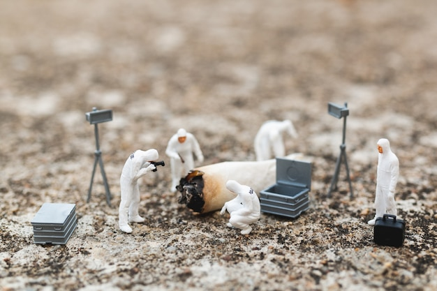 Miniature people: police and detective finding proof from old cigarette in crime scene