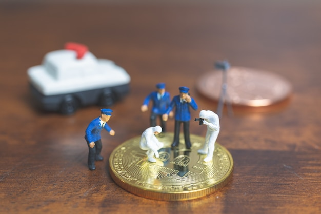 Miniature people : police and detective standing in front of cryptocurrency bitcoin