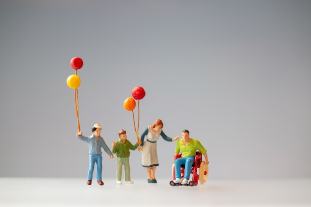 Miniature people positive family taking care of their disabled father