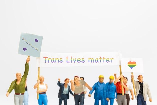社会的距離を奨励するトランスジェンダーの旗の看板を持っているミニチュアの人々の抗議者、トランスの権利の概念