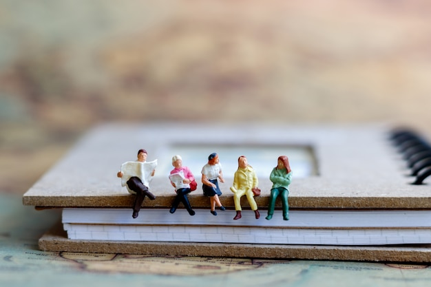 Miniature people reading  book, concept of the education or business.