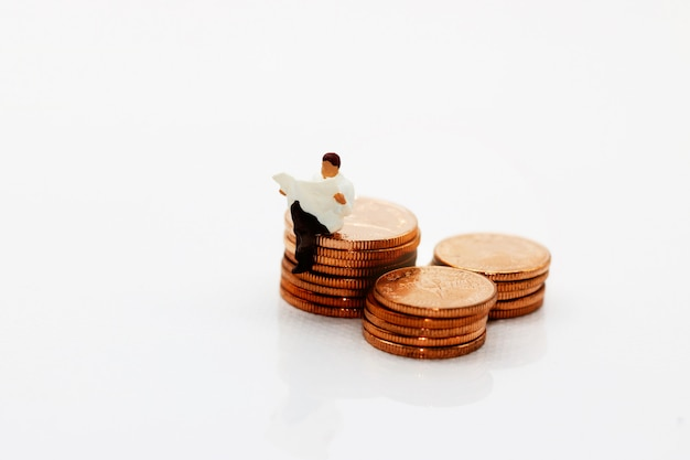 Miniature people reading book on step of coin money.