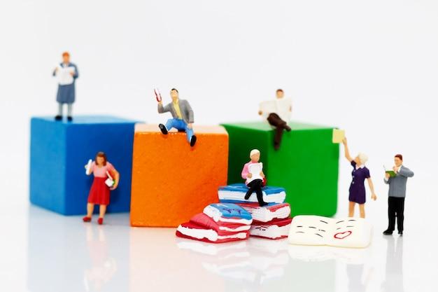 Miniature people reading books