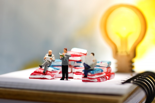 Miniature people reading and sitting on book with lamp idea .