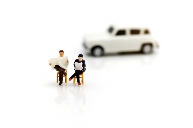 Miniature people reading and sitting on car  using as background, education concept.