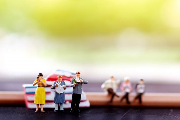 Miniature people reading with books.