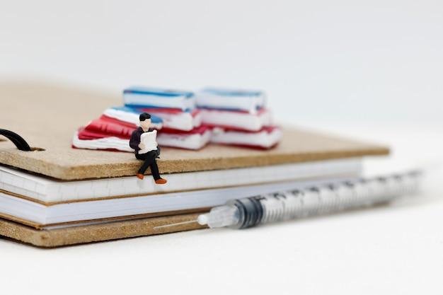 注射器と本で読むミニチュアの人々。教育コンセプト。