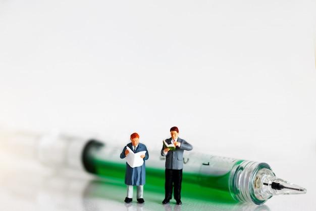 注射器で読むミニチュアの人々。医療コンセプトの教育。