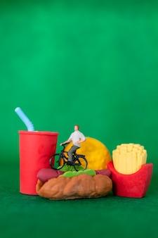미니어처 사람들은 패스트 푸드, 건강에 해로운 먹는 개념에 자전거를 타고