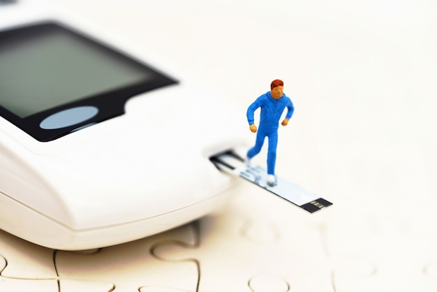 Miniature people running on a glucose meter of diabetes
