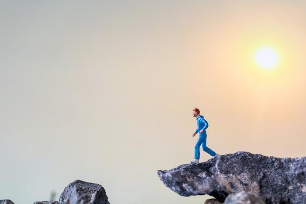 ミニチュアの人々:岩の崖の上を走る、健康とライフスタイルのコンセプト