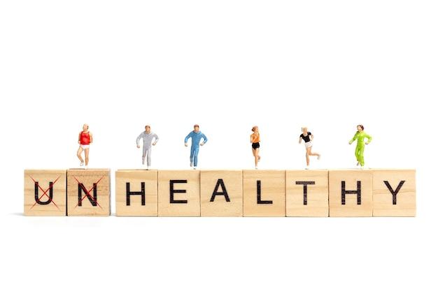 흰색 바탕에 나무 편지 블록에서 실행하는 미니어처 사람들 건강 개념
