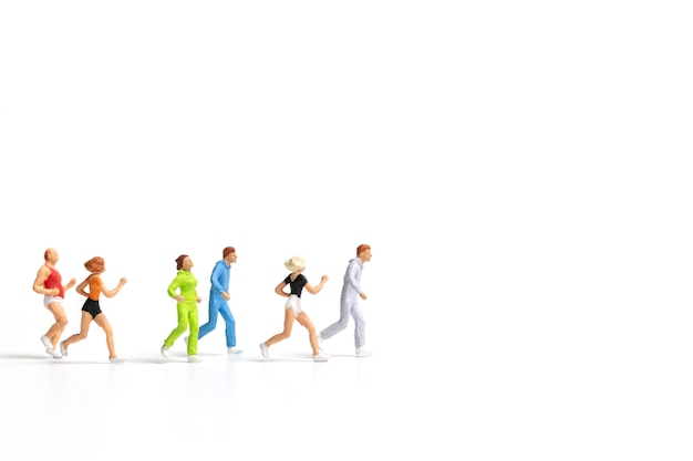 Miniature people running on white background