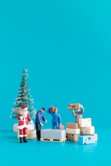 미니어처 사람들, 산타 클로스와 그의 작업자 팀은 매년 크리스마스 이브에 선물, 크리스마스 및 새해 복 많이 받으세요 개념을 전달할 준비를 하고 있습니다.