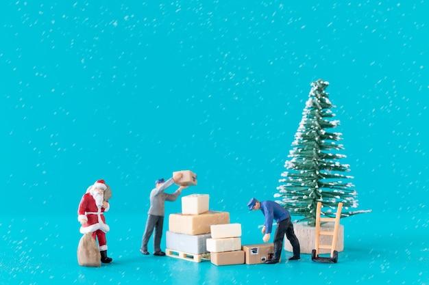 미니어처 사람들 산타 클로스와 그의 작업자 팀이 선물을 준비하고 있습니다