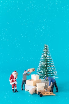 Miniature people santa claus and his worker team are preparing gifts