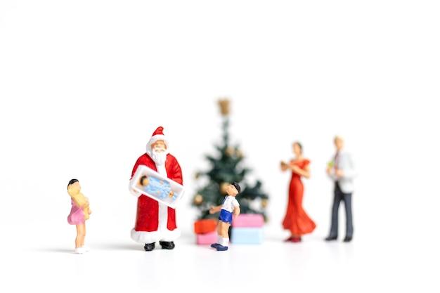 미니어처 사람들 : 산타 클로스 행복 한 가족, 크리스마스와 새 해 복 많이 받으세요 개념 선물을 들고.