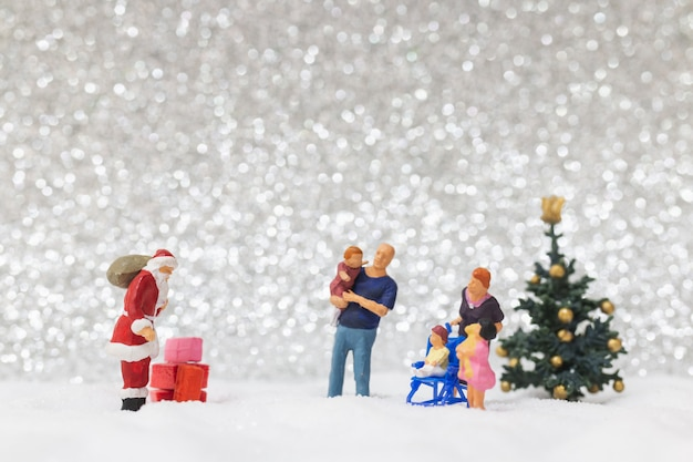 Miniature people: santa claus and kids with snow background