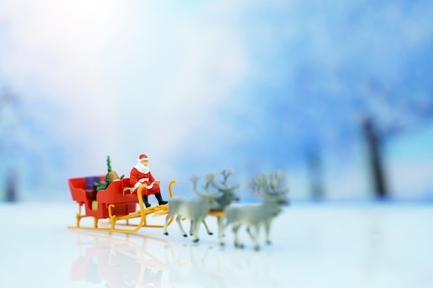 Miniature people: santa claus sitting reindeer sleigh with greeting or postal card and christmas tree.