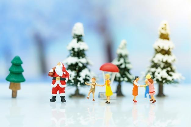 Миниатюрные люди: санта-клаус с детьми, играющими веселье со снегом и елкой.