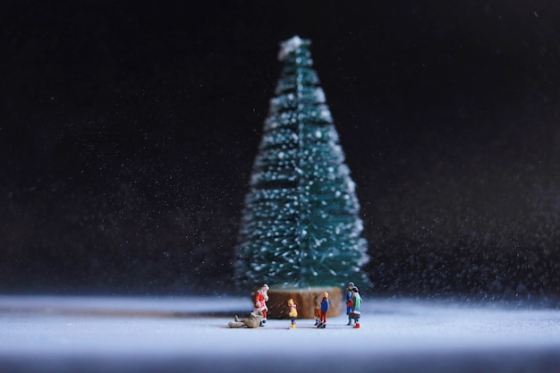 Miniature people santa claus with people under the big christmas tree.
