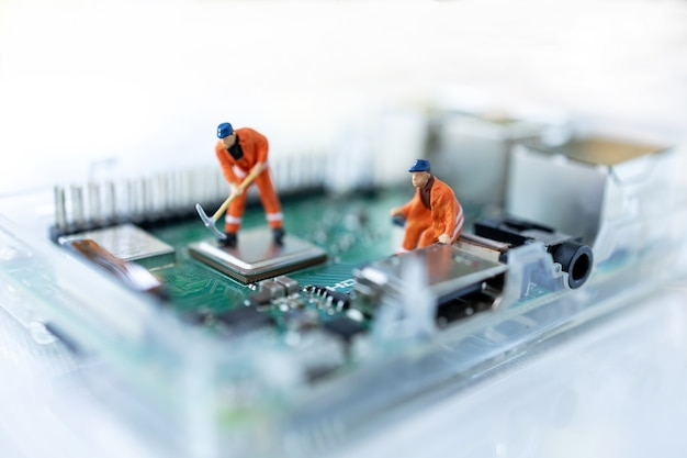 Miniature people searching or checking for bugs and issue on microchip, mainboard of computer.