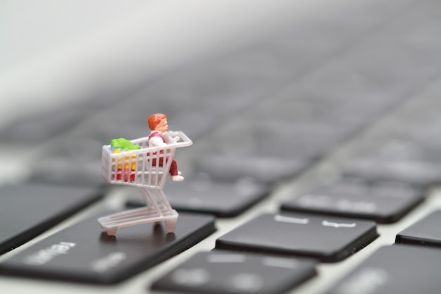 Miniature people: shopper press enter on computer keyboard as payment online from home
