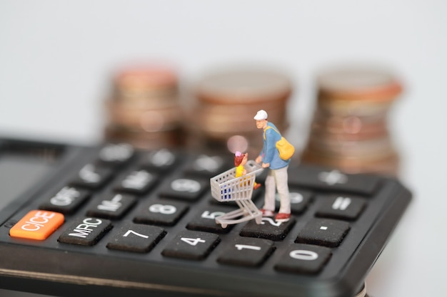 Miniature people: shopper and trolley walking on calculator with blur coins behind