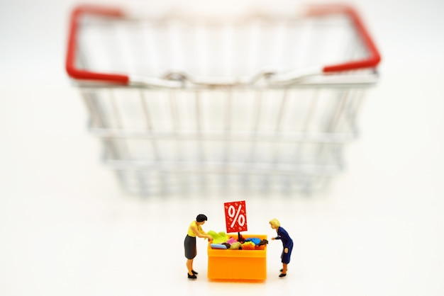 Miniature people: shoppers buy goods on sale with discount tray and shopping cart.