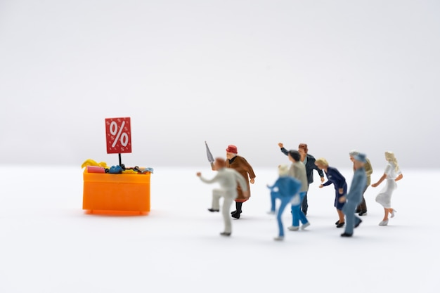 Miniature people, shoppers running to discount tray for shopping discounted items
