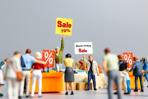 미니어처 사람들, 할인된 품목 쇼핑을 위한 할인 트레이가 있는 쇼핑객, 블랙 프라이데이 개념