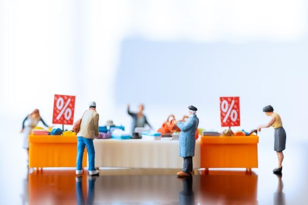 Миниатюрные люди, покупатели с лотком для скидок для покупок товаров со скидкой