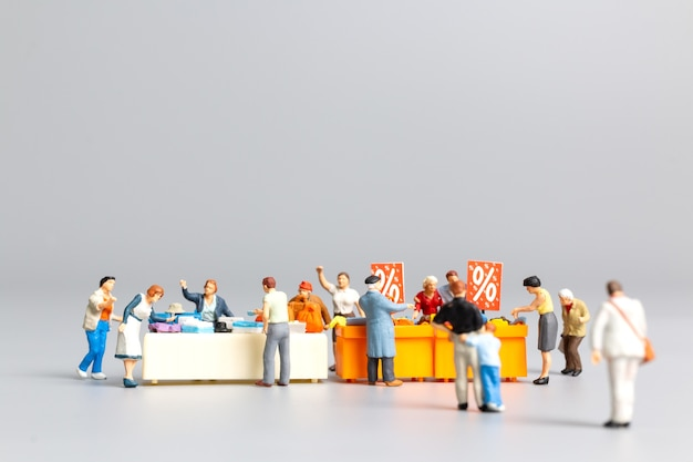 Miniature people , shoppers with discount tray for shopping discounted items ,  black friday concept